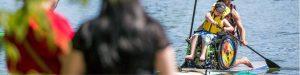 un enfant faisant du stand up paddle board adapté accompagné d'un partenaire de propulsion