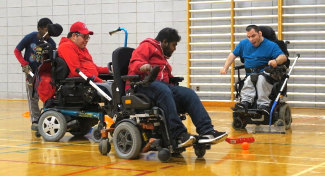 3 jeunes hommes jouant au powerchair hockey en fauteuil motorisé
