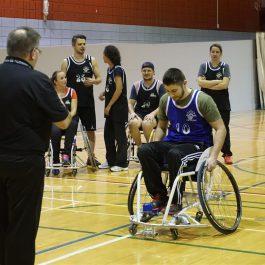 Entraineur donnant des instructions à une personne jouant au basketball en fauteuil roulant